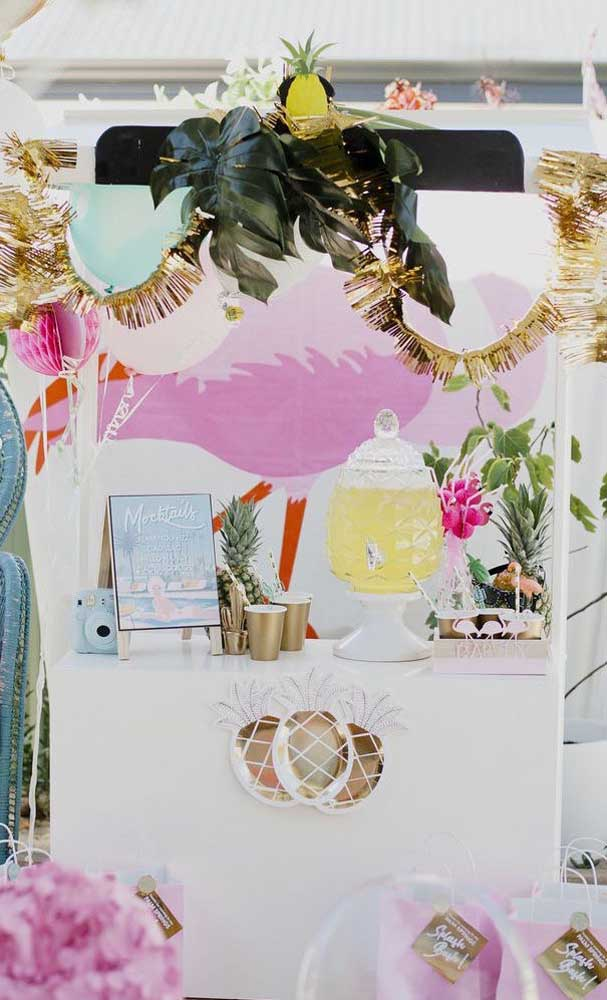 Decoração de festa ao estilo tropical feita ao ar livre; no cenário, abacaxis, folhas e flores exóticas