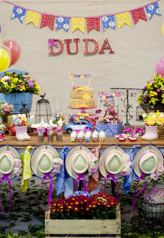 Use vários elementos decorativos para montar a mesa de festa junina.