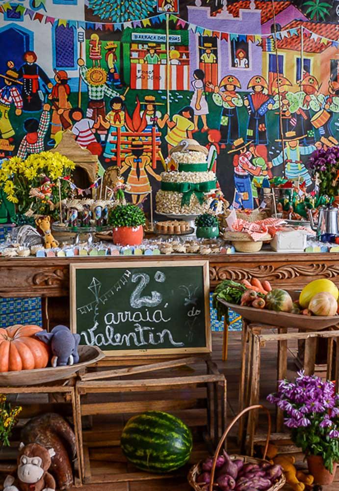 Olha que painel fantástico para decorar uma festa junina. A mesa caprichada complementa o cenário.