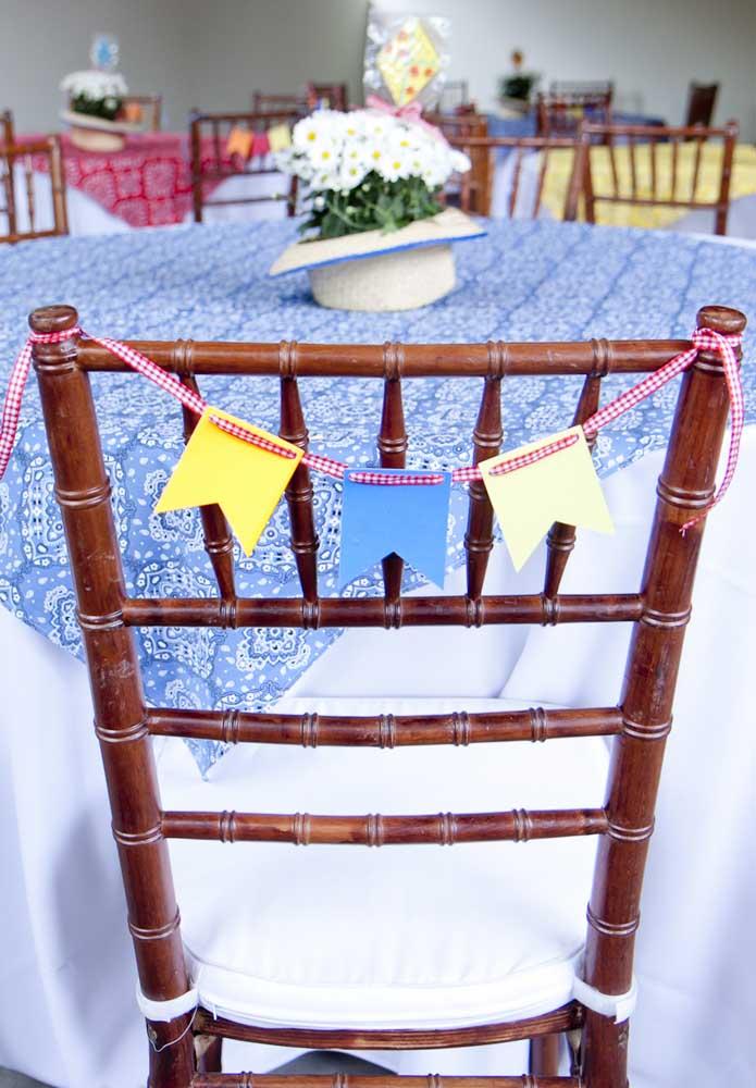 As cadeiras também merecem ser decoradas. Para isso, enfeite com bandeirinhas.