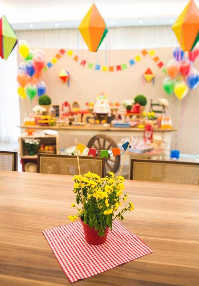Coloque vasos com flores e bandeirinhas para decorar a mesa dos convidados.