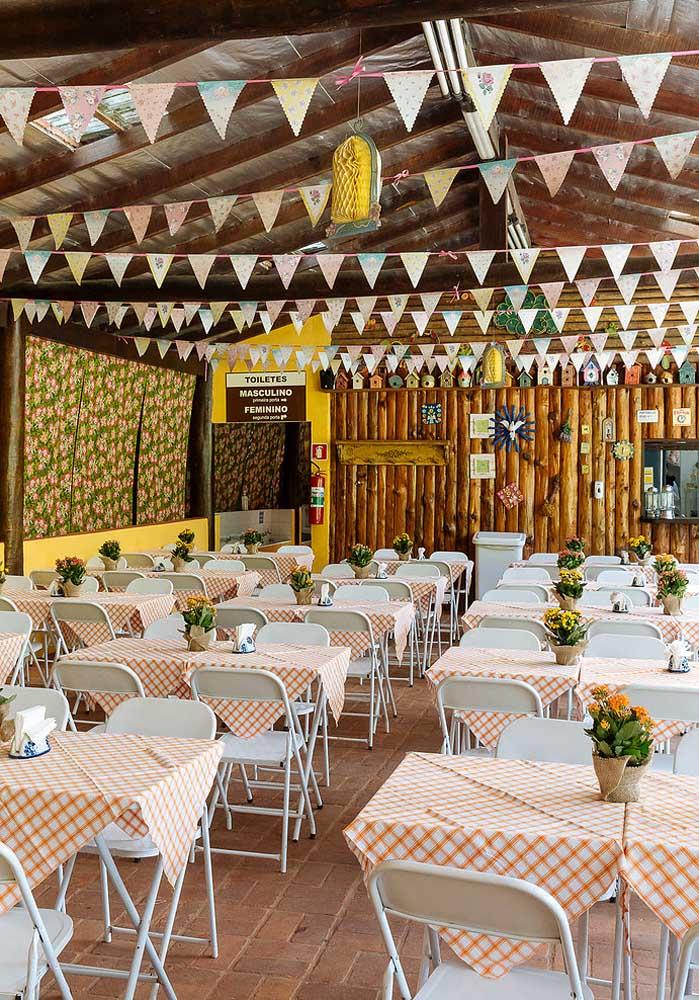 Dá para fazer uma decoração simples para sua festa junina apenas usando tecido xadrez e bandeirinhas.