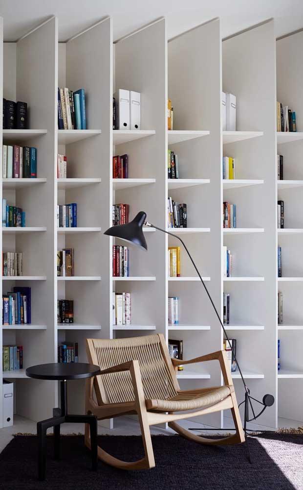 Uma poltrona confortável, uma mesinha lateral e uma luminária estrategicamente posicionada: elementos indispensáveis em uma biblioteca pessoal