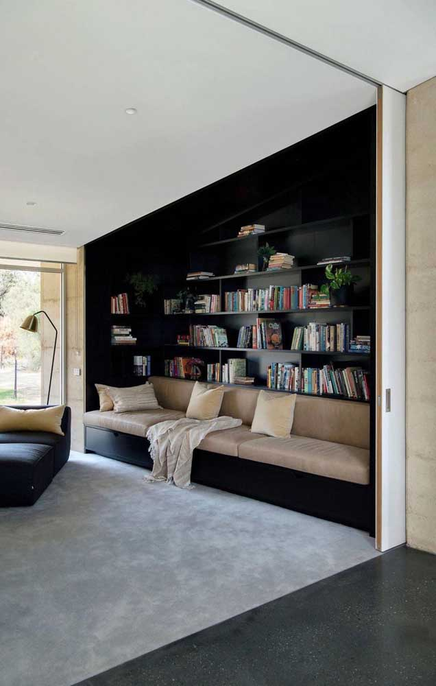 Essa sala de estar moderna optou por colocar a biblioteca atrás do sofá; uma ótima alternativa