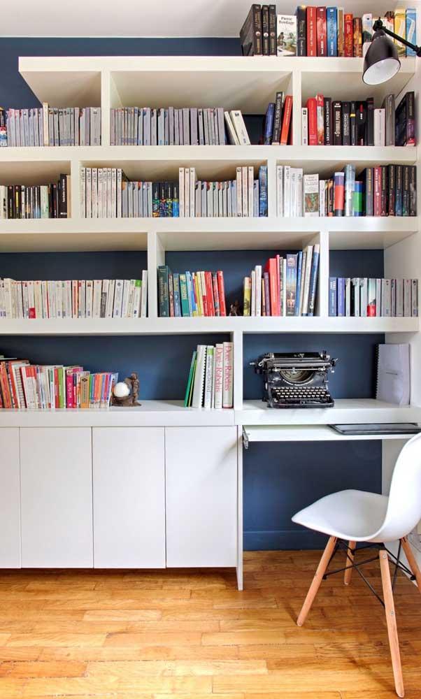 A parede azul petróleo do home office ajudou a destacar os livros que vem na frente