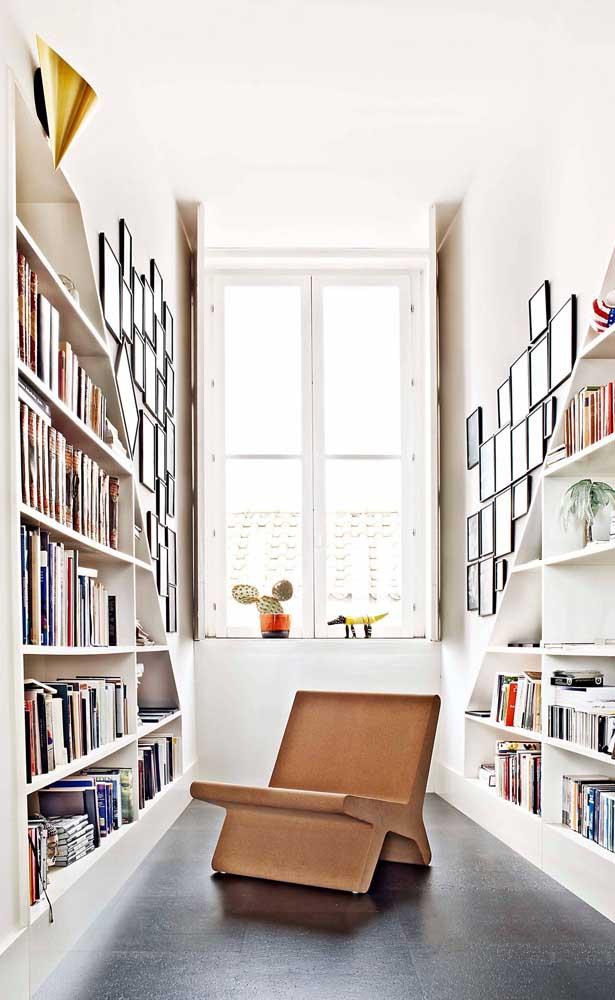 Essa pequena biblioteca super iluminada conta com uma poltrona de design e nichos em formato triangular
