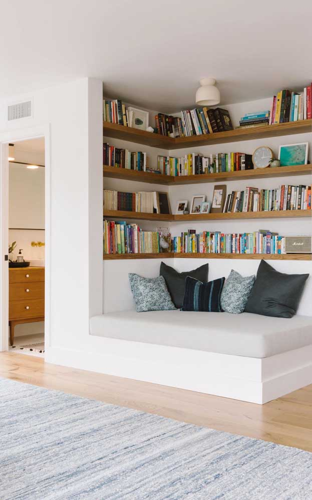 Já esse outro quarto aproveitou o espaço maior para criar um espaço de leitura mega confortável