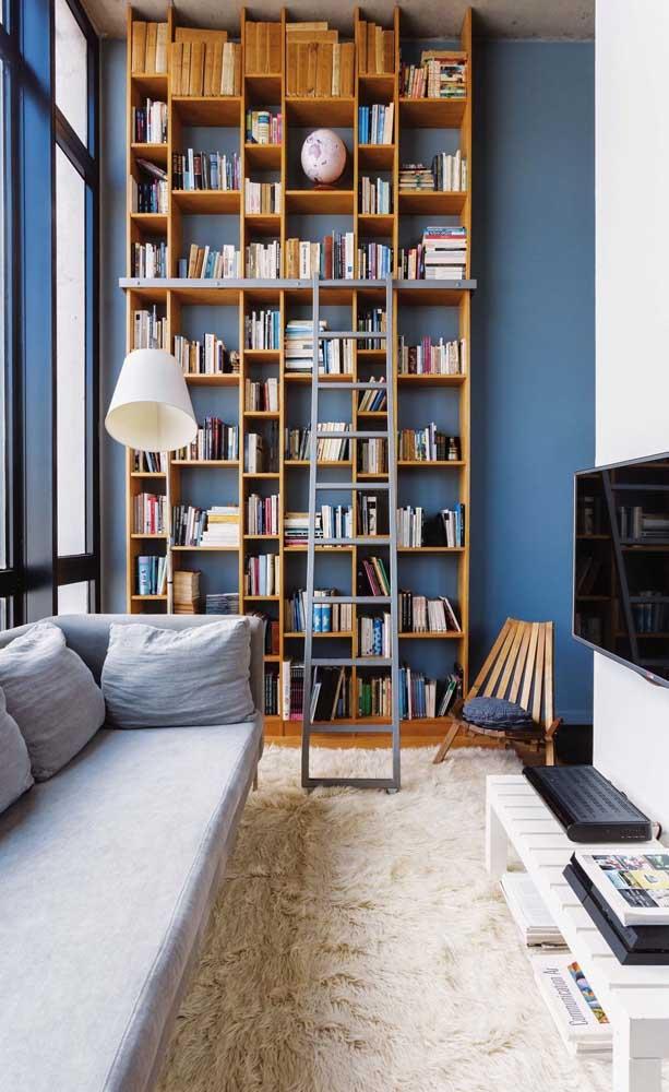 Nessa sala, a parede azul ganhou nichos de madeira para organizar a mini biblioteca
