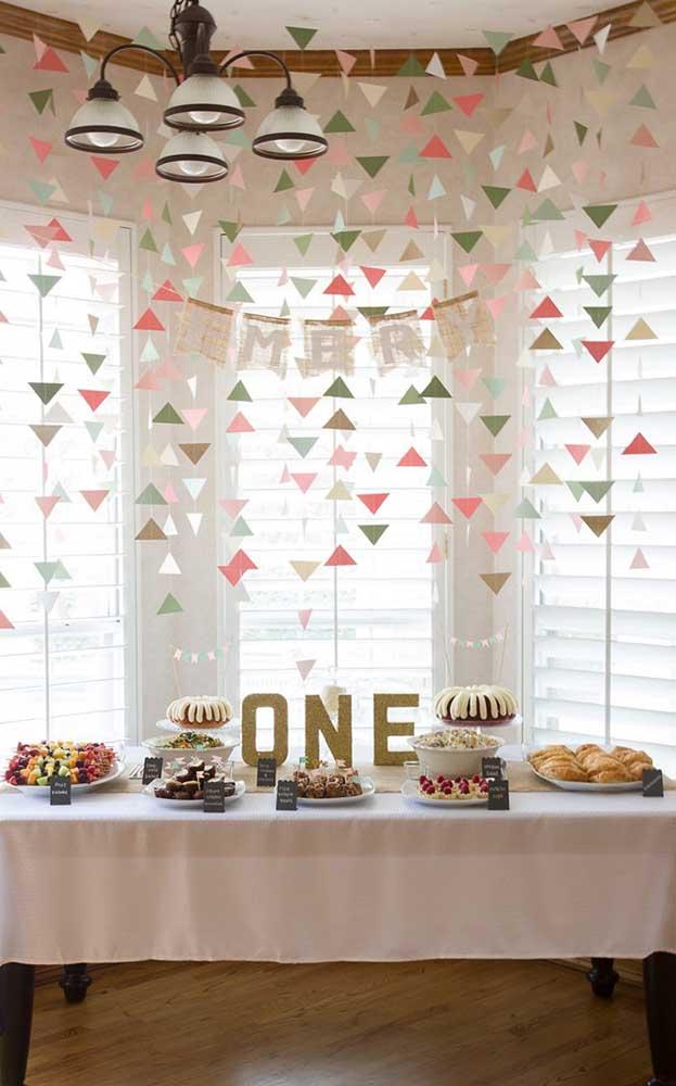 Mesa de doces e petiscos das Bodas de Papel decorada com recortes coloridos suspensos