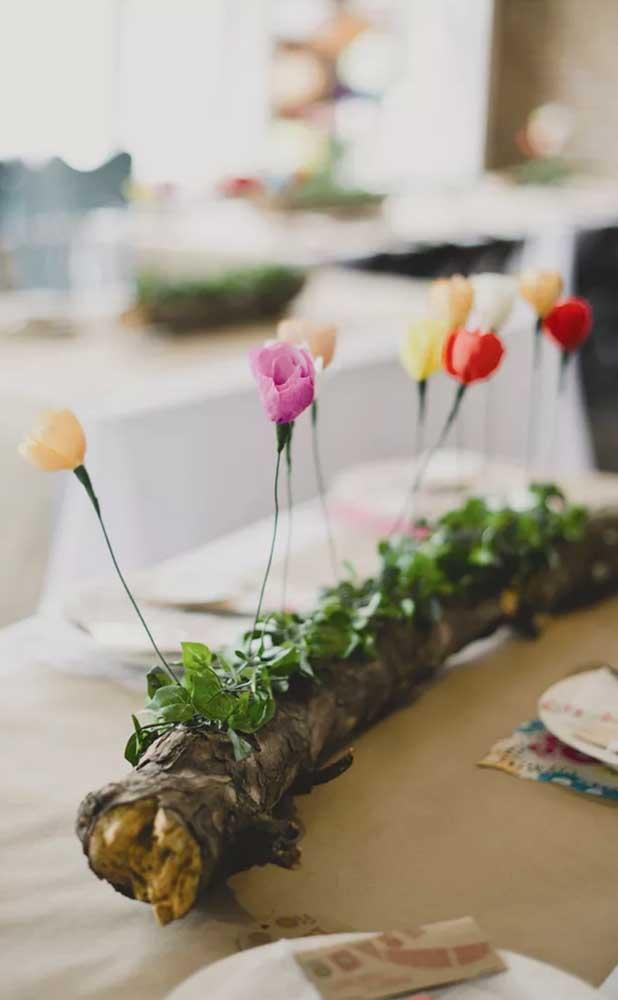 A mesa da festa de Bodas de papel foi decorada com flores de papel presas em um galho rústico de árvore, encantador!