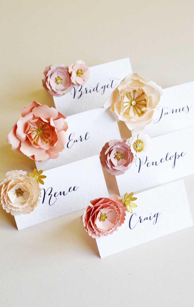 Os marcadores de mesa ficaram lindos com o detalhe das flores de papel