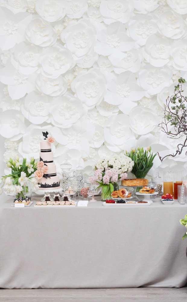 Que incrível o visual dessa mesa de bolo e doces para a festa de Bodas de Papel! Repare no imenso painel de flores de papel gigantes aos fundos