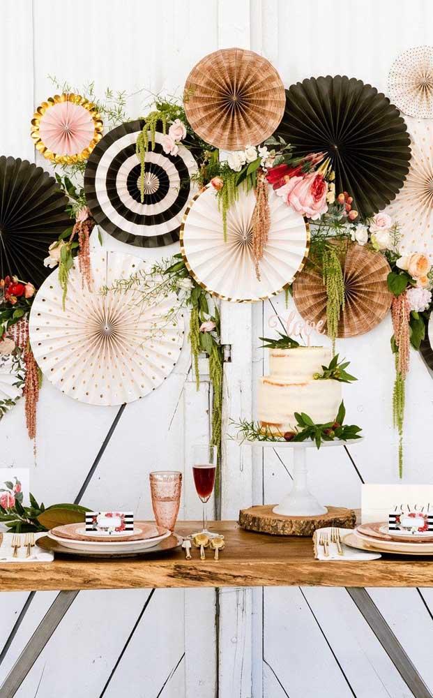 Enfeites de papel em estilo leque decoram a mesa de bolo das bodas do casal