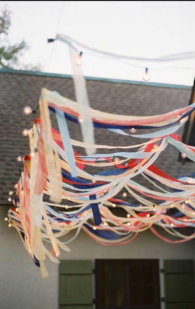 Se a festa for ao ar livre, uma boa opção é decorar com fitas de papel colorido e luzes