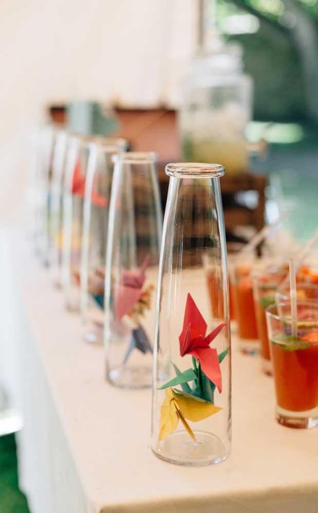 Que linda opção de decoração para as Bodas de Papel: garrafas de vidro com origamis coloridos dentro