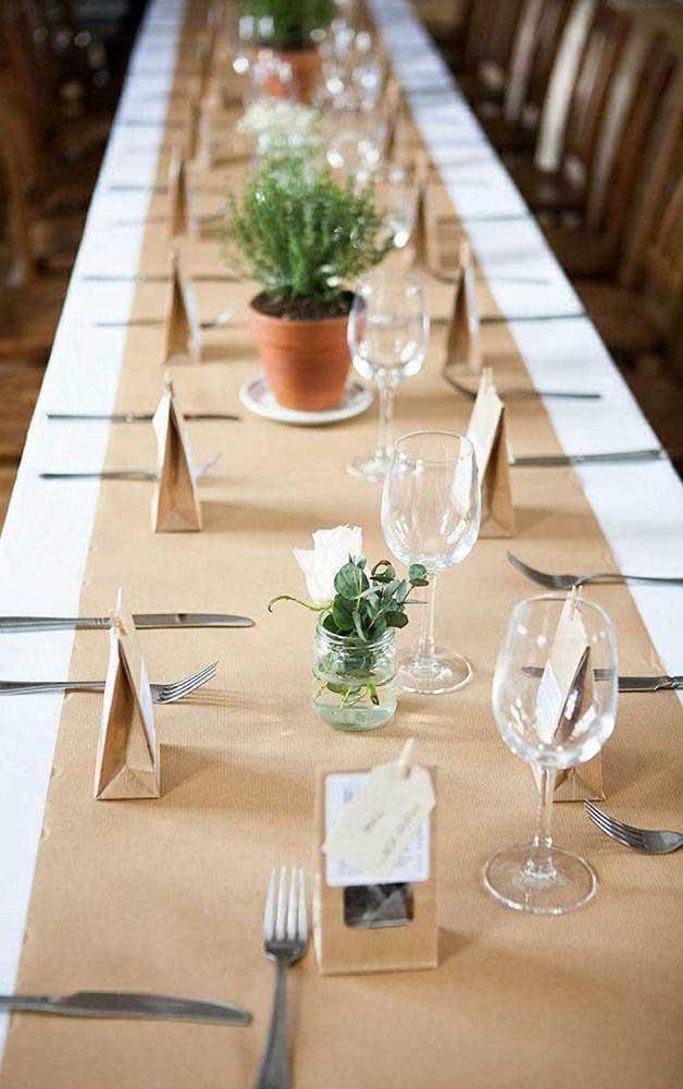 Mesa posta para um jantar de Bodas de Papel, com marcação dos lugares, lembrancinha nas taças e centro da mesa em papel