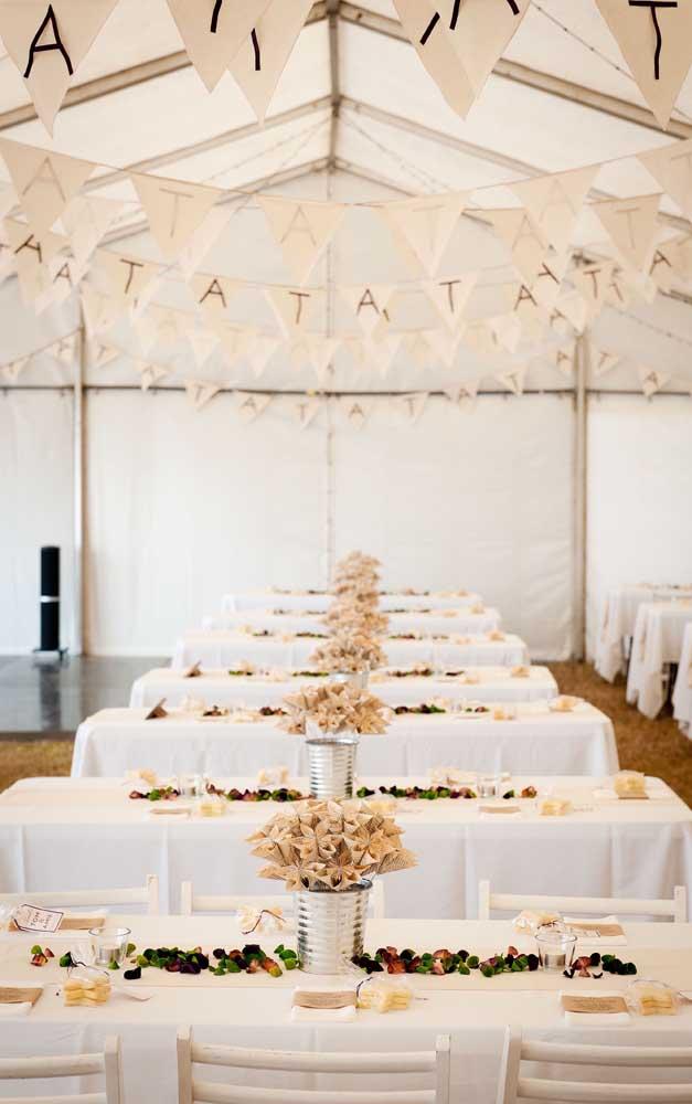Flores de papel dentro de latas reaproveitadas fazem a decoração dessa outra celebração de bodas