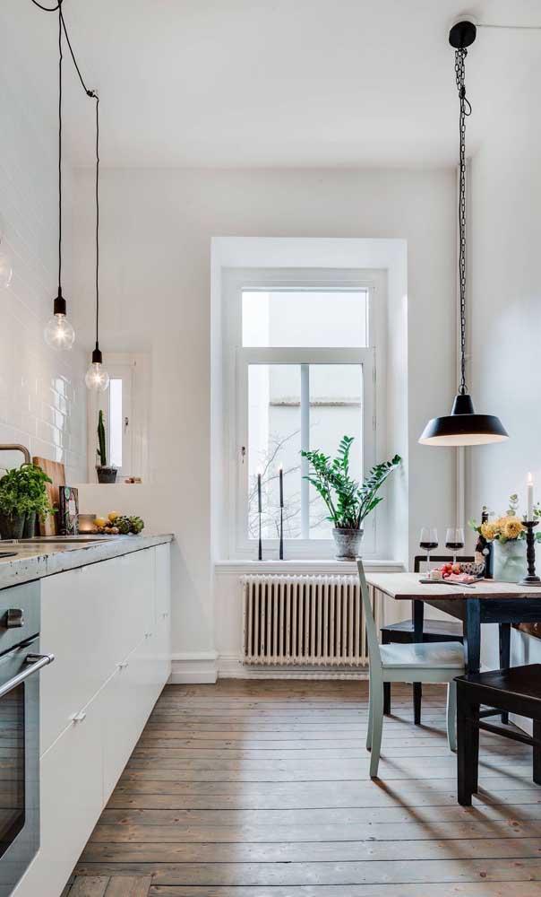 Cozinha pequena com mesa rústica de madeira encostada na parede