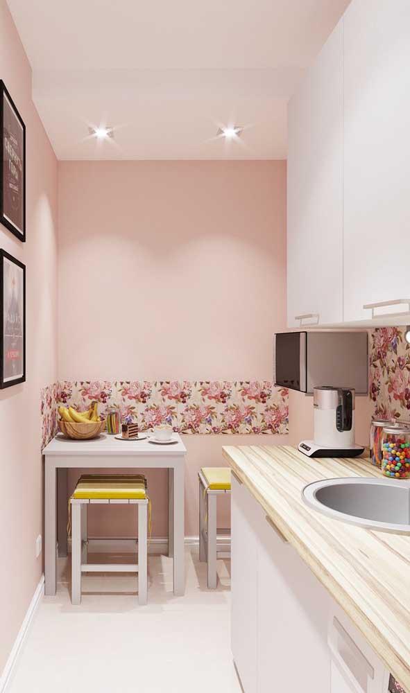 Essa cozinha pequena e delicada traz um conjunto de mesa com bancos na cor branca