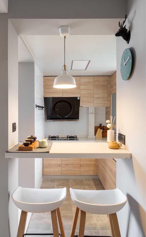 O espaço ocioso entre a cozinha e a sala de estar foi preenchido com uma mesa bancada acompanhada de banquetas altas