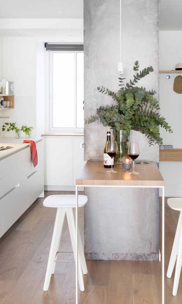 O espaço de passagem dessa cozinha foi reduzido para dar lugar a uma pequena mesa balcão