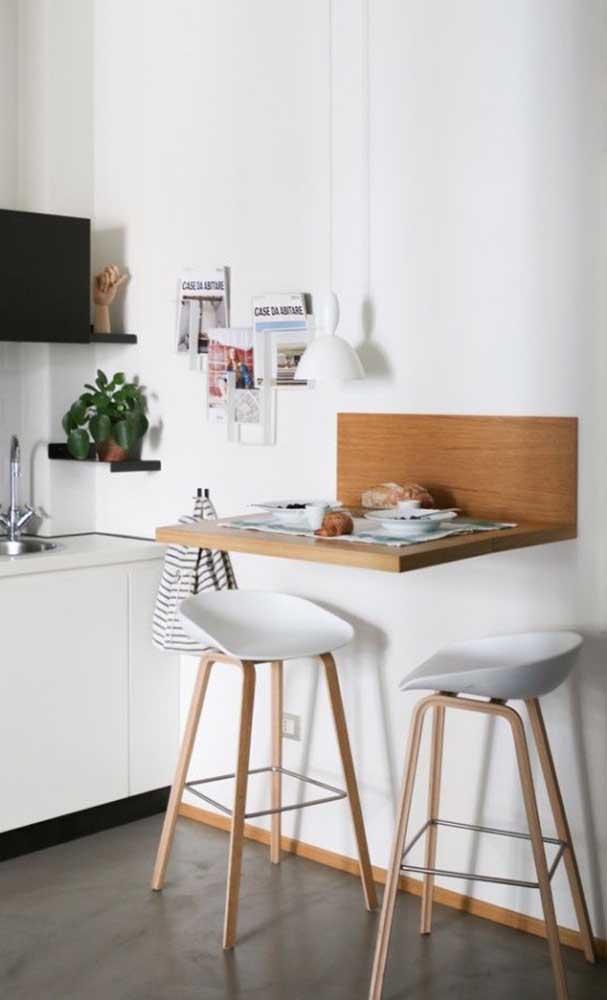 A simplicidade dessa pequena mesa balcão é contrastada com o design moderno das banquetas