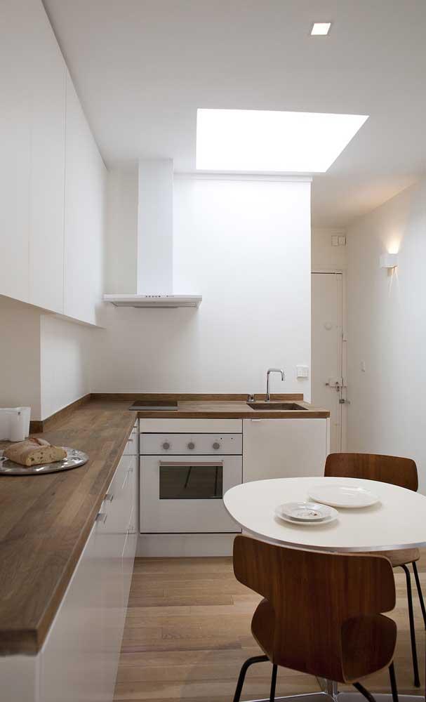Mesa redonda pequena e simples valorizada pelas cadeiras de design que a acompanham