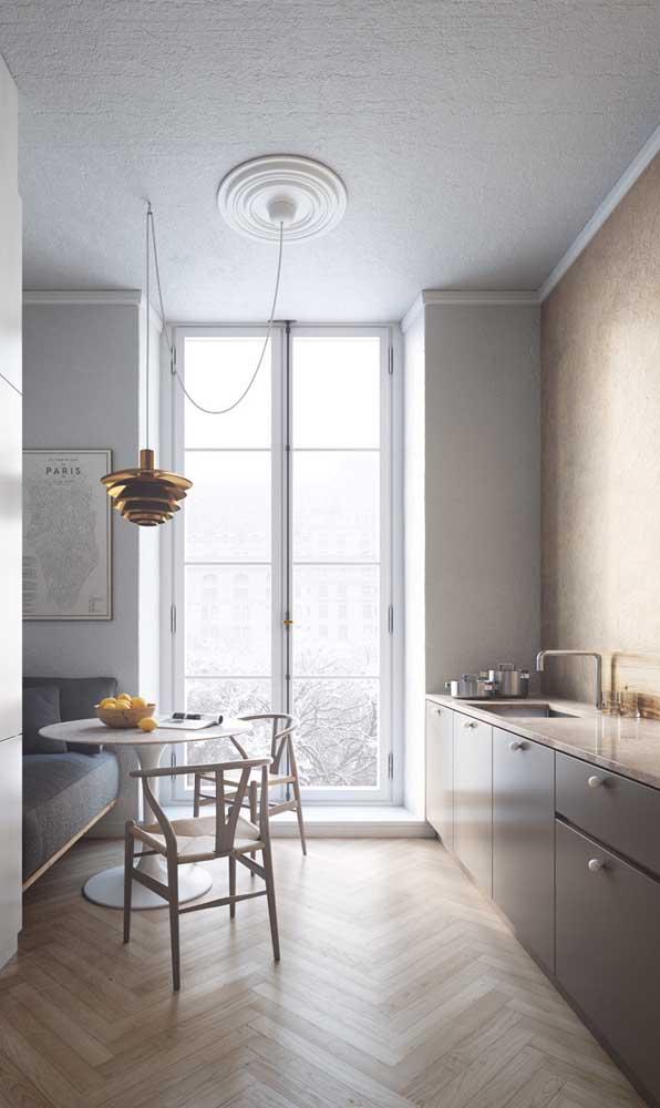 Uma maneira de valorizar a mesa pequena da cozinha é instalando uma luminária lindona sobre ela