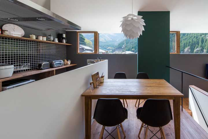 Essa cozinha moderna em estilo americano trouxe uma mesa retangular pequena de madeira