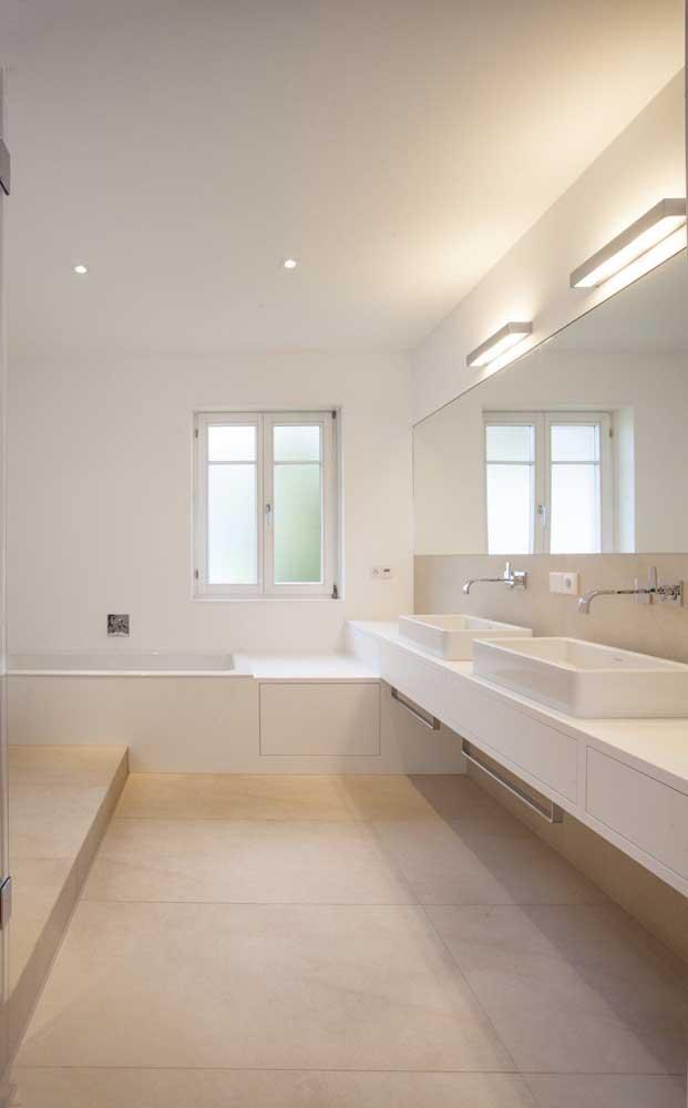 Nesse banheiro amplo, a cor marfim quebra a monotonia predominante do branco