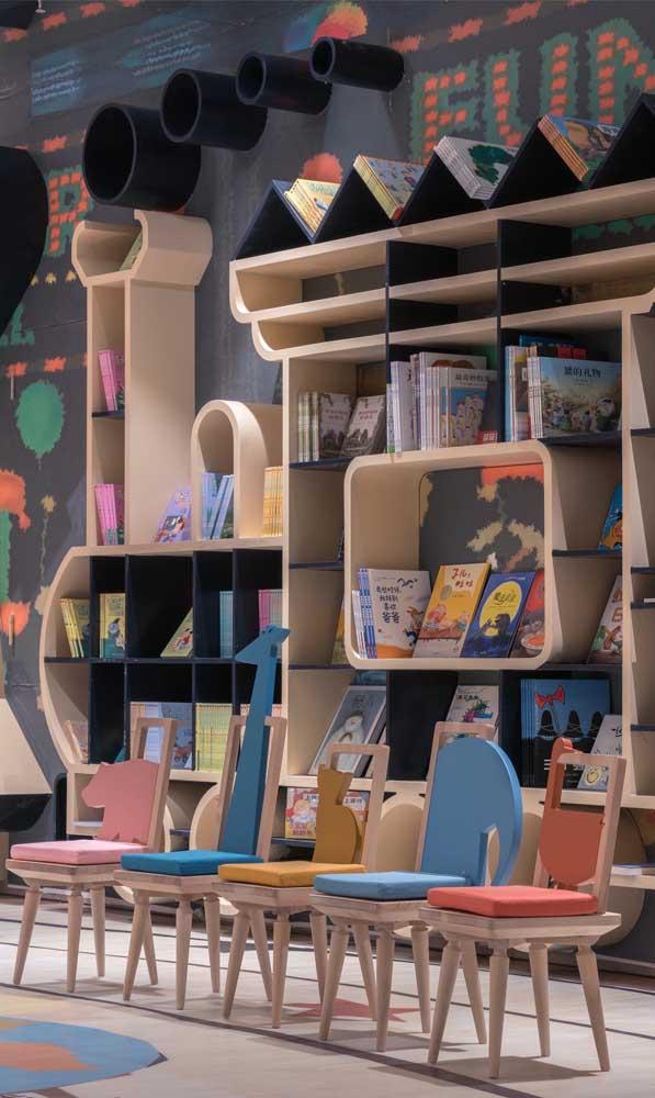 Olha o charme dessas cadeiras de madeira com desenhos de animais; repare ainda na parede desenhada aos fundos