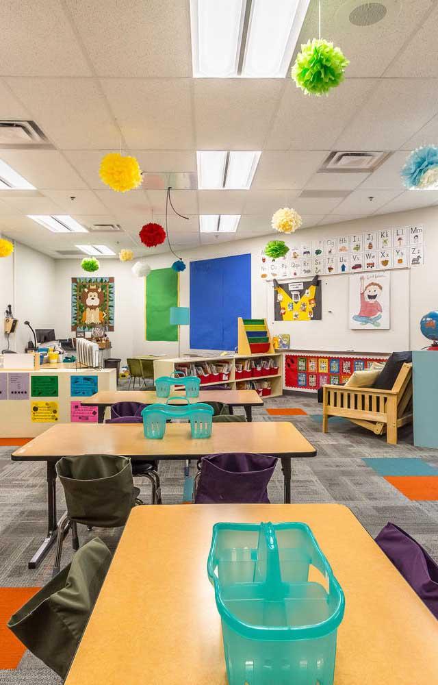 Já a decoração da sala de aula infantil conta com enfeites de papel no teto e cestinhos coloridos sobre as mesas