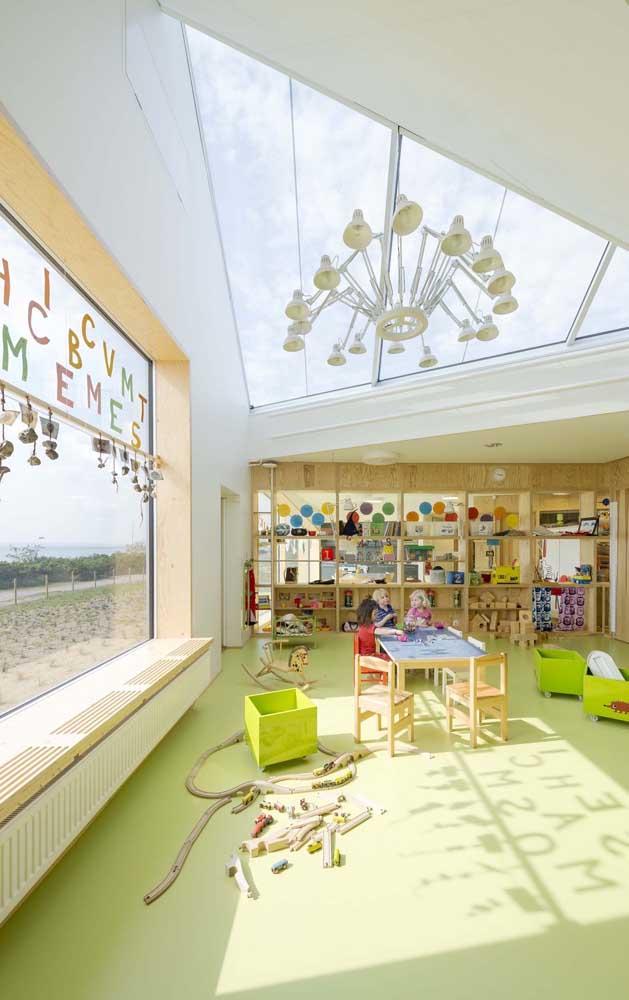 A sala de aula cheia de luz natural trouxe brinquedos artesanais como forma de decoração; a cor viva do piso também merece destaque