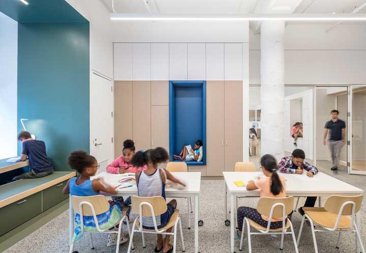 A área de leitura dessa sala de aula traz mesas, nichos e sofás para acomodar os alunos