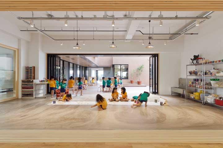 Sala de aula ampla integrada à área externa da escola; repare que os alunos tem total liberdade para ocupar o espaço