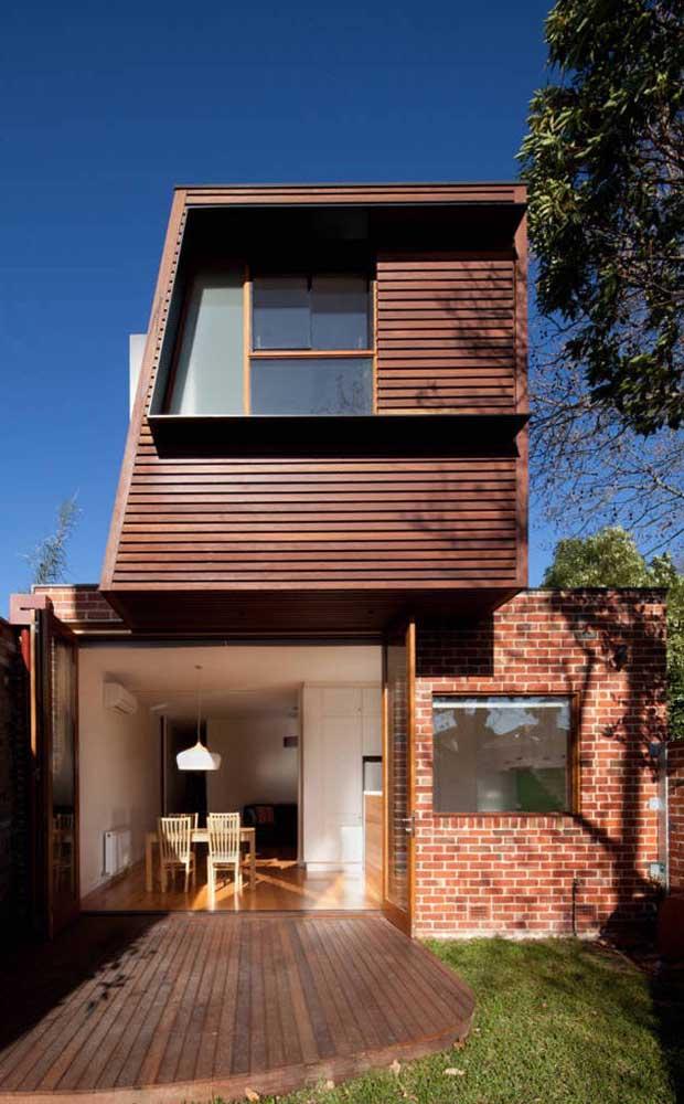 Fachada de casa duplex moderna com acabamento em madeira e tijolinhos à vista; repare que ainda sobrou espaço para um jardim