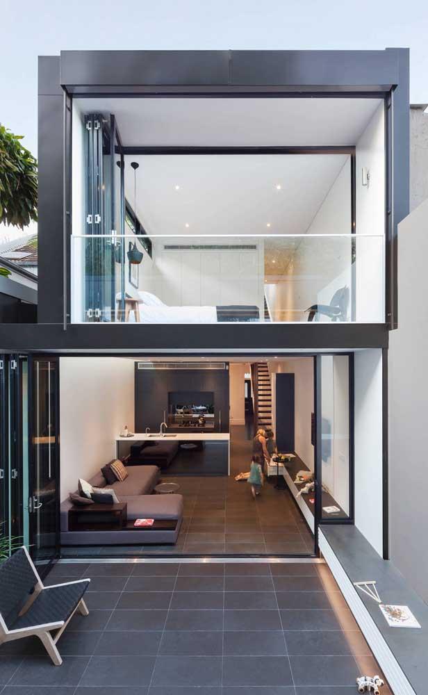 A fachada de vidro da casa duplex permite uma integração total com a área externa do imóvel.