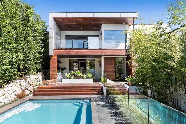 Maravilhosa inspiração de casa duplex com piscina; repare que a planta ainda priorizou um jardim e uma varanda aconchegante