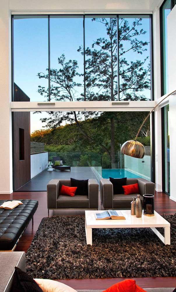 Sala de estar da casa duplex com parede de vidro fazendo a integração direta com a área da piscina lá fora