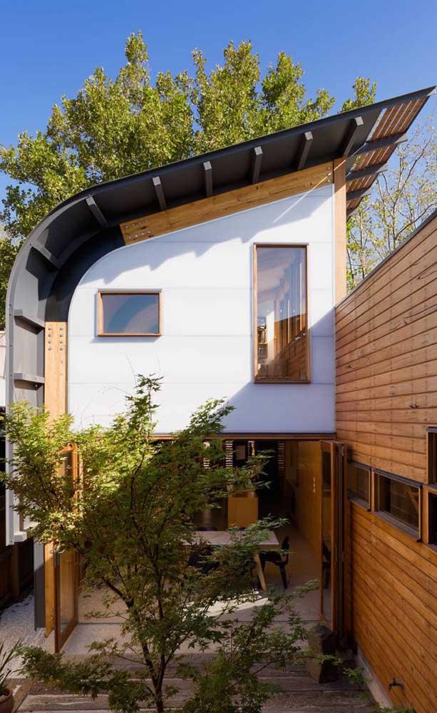 Casa duplex com um telhado super contemporâneo; a fachada em madeira é outro destaque da construção
