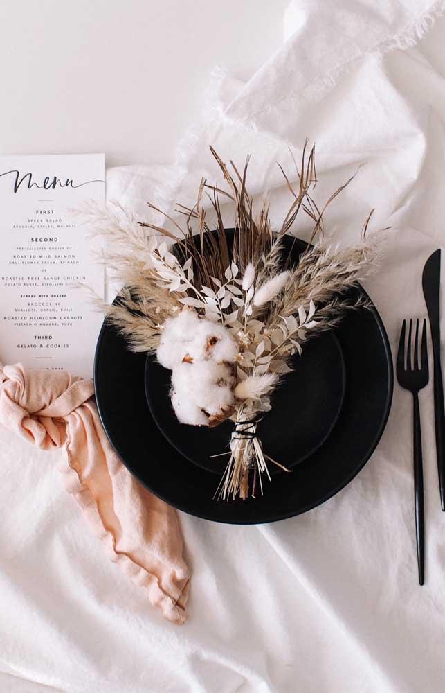 Arranjo rústico feito com ramos de algodão decorando a mesa de jantar das Bodas