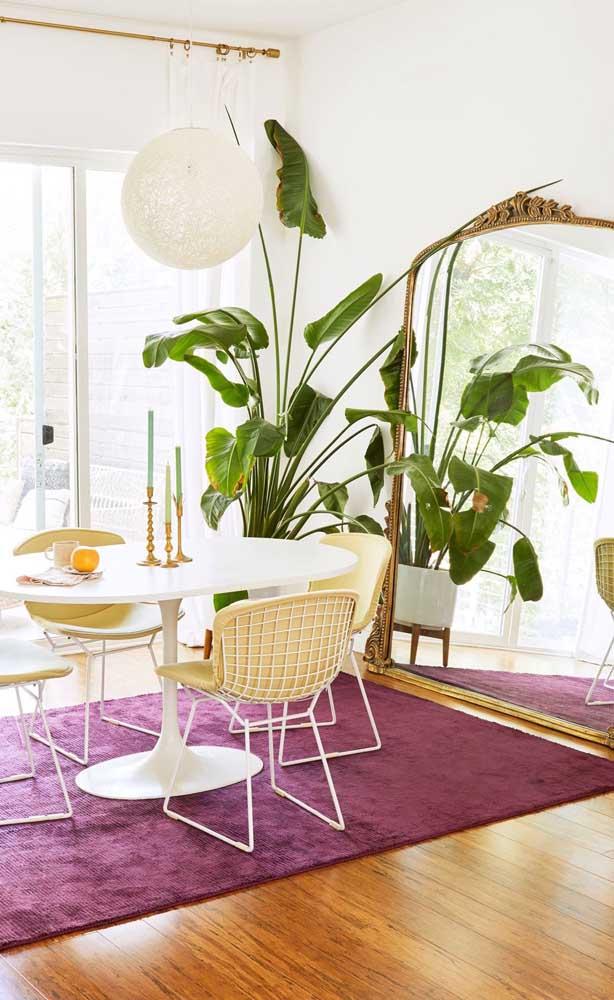 Sala de jantar decorada com espelho no chão; destaque para a moldura vintage na peça