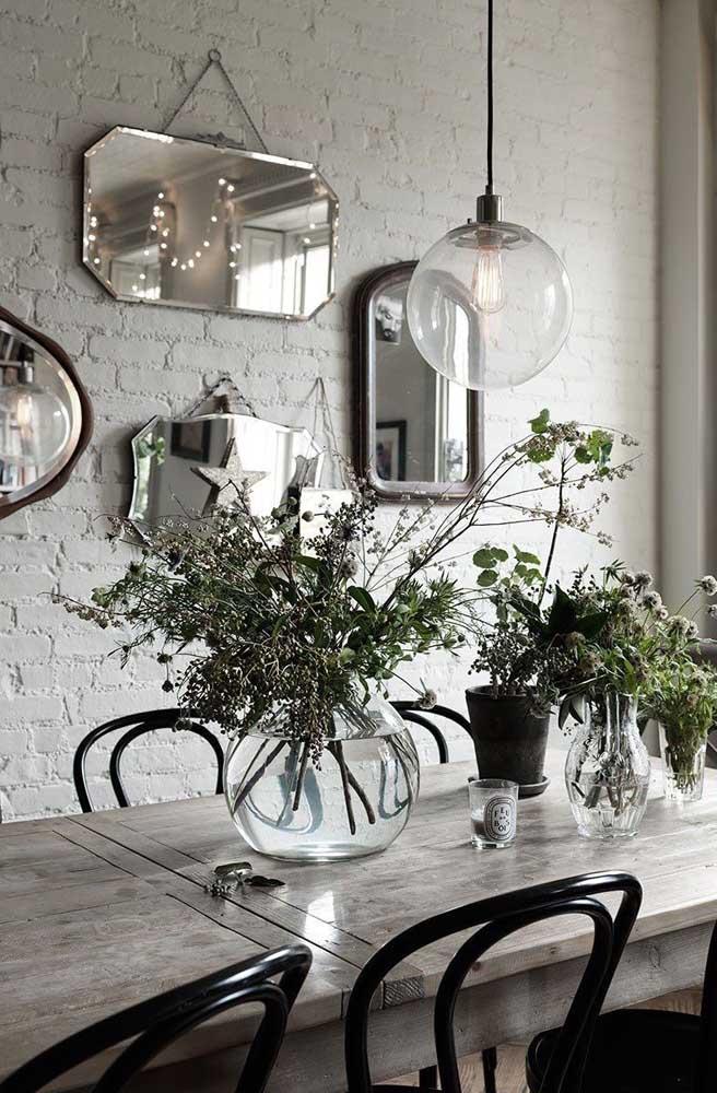 Essa sala de jantar de estilo rústico apostou em espelhos de formatos variados na parede