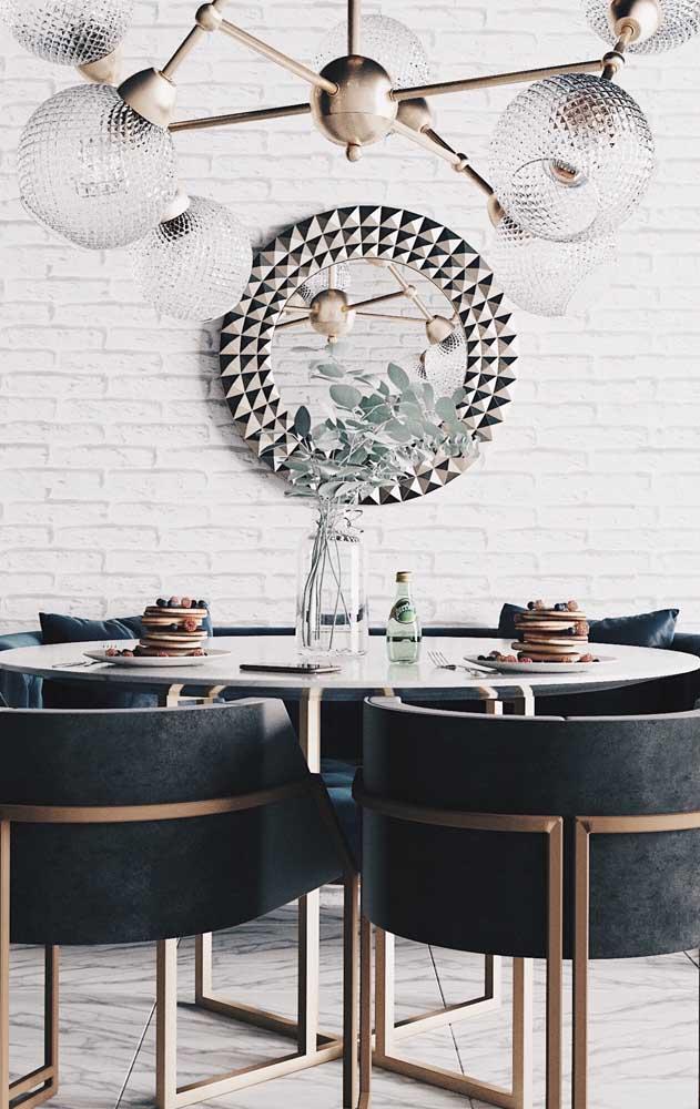 Aqui, o espelho redondo reflete e valoriza a bela luminária da sala de jantar