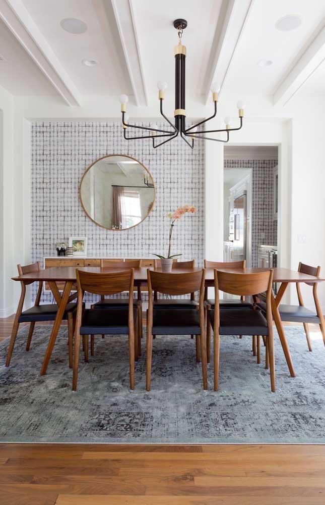 Sala de jantar grande decorada com espelho redondo na parede principal; repare que a moldura da peça combina perfeitamente com a mesa e as cadeiras
