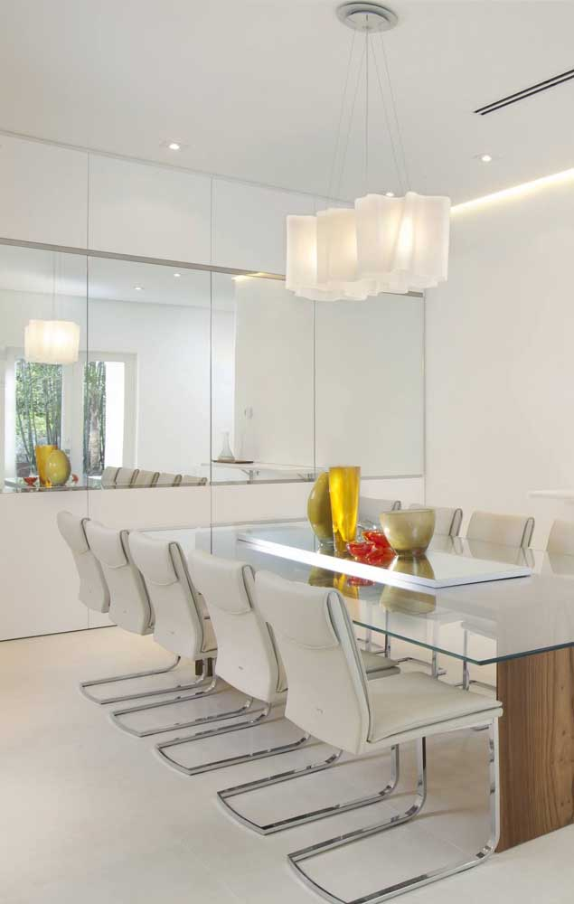 Profundidade e amplitude para essa sala de jantar clean e moderna decorada com espelhos
