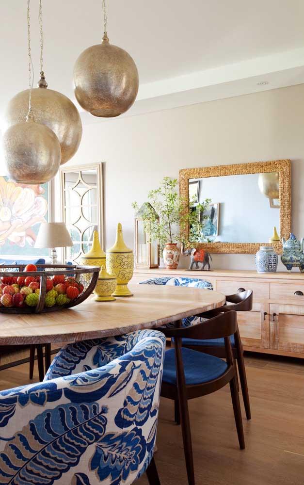 Espelho simples sobre o aparador da mesa de jantar; repare que a moldura feita com pastilhas é que valoriza a peça