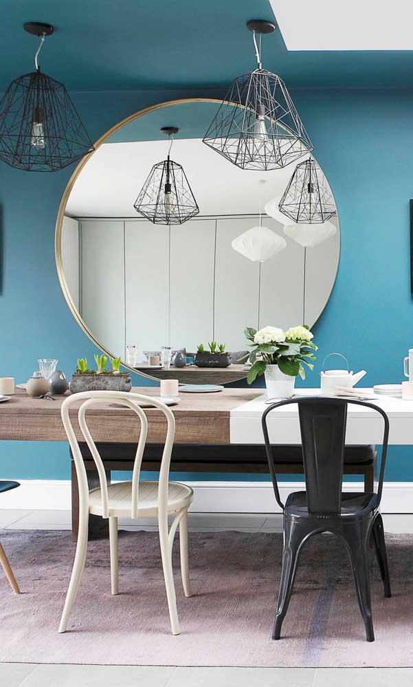 O fundo azul da parede garantiu todo o destaque para o espelho redondo da sala de jantar