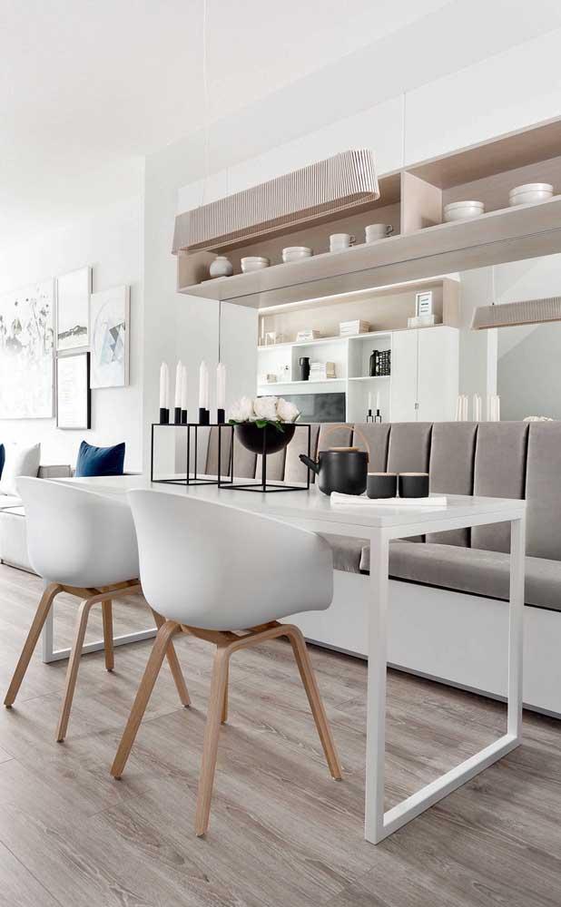 O espelho atrás da mesa de jantar é sempre uma opção certeira para quem deseja ampliar o ambiente