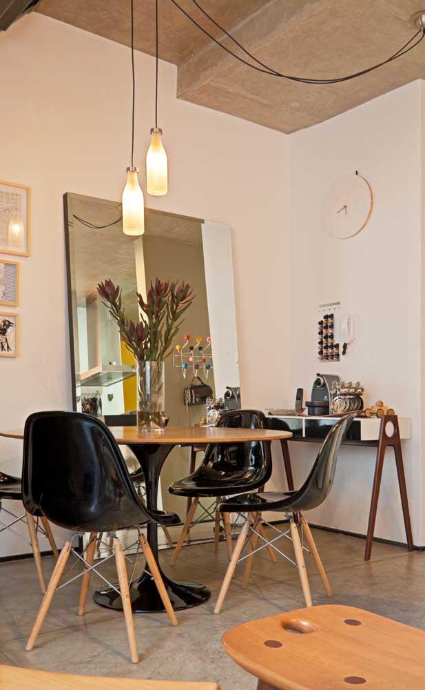 Essa sala de jantar moderna trouxe um espelho grande e sem moldura para ser usado diretamente no chão